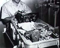 Chimpanzé Enos usando uma roupa espacial e preso à poltrona de vôo com um manipulador preso em suas mãos enquanto está sendo preparado para entrar na cápsula do Mercúrio-atlas 5